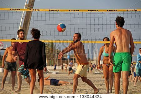Barcelona, Spain - June 28, 2016: People playing beach volley on Barceloneta beach