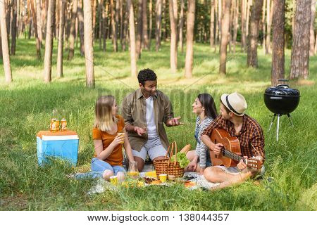 Cheerful young man is telling story to his friends. They are looking at him with interest and smiling. Men and women are sitting on grass in forest