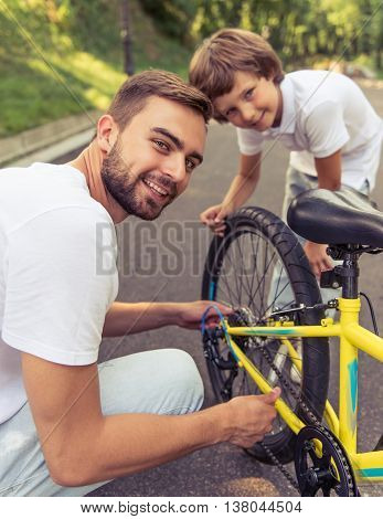Handsome young dad and his cute little son are riding bikes in park. Both are looking at camera and smiling while father is examining his son's bicycle
