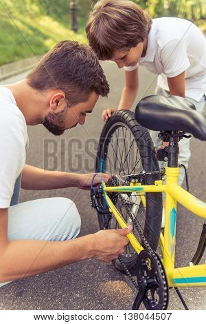 Handsome young dad and his cute little son are riding bikes in park. Father is examining his son's bicycle