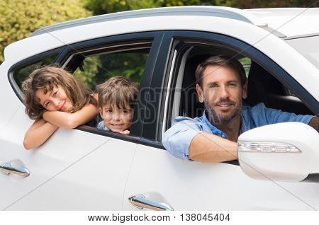 Children sitting in the car looking out windows. Cute children in car going camping with father. Small young family travelling with rental car and looking at camera.