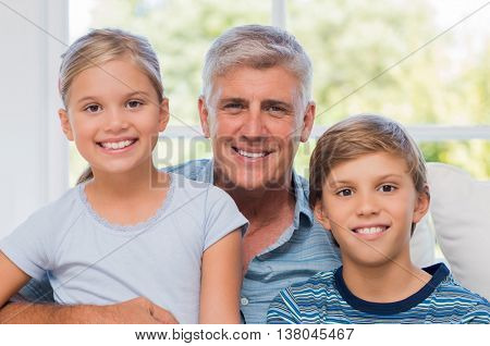 Grandpa sitting with boy and girl looking at camera. Cheerful Grandfather embracing grandson and granddaughter on couch. Portrait of smiling grandchildren with older man.