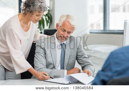 Senior manager helping senior employee complete the report. Team of businessman and businesswoman working on a business documet. Senior partners working together reviewing contract at office.