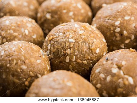 sesame laddu or tulgul or til gul laddu or ladu in brass plate with huldi and kumkum, indian traditional festival in january, indian sweet food, indian rituals, tilgul cake or vadi