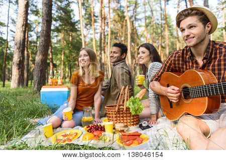 Young friends are enjoying nature together. They are sitting on grass and smiling. Man is playing guitar with pleasure