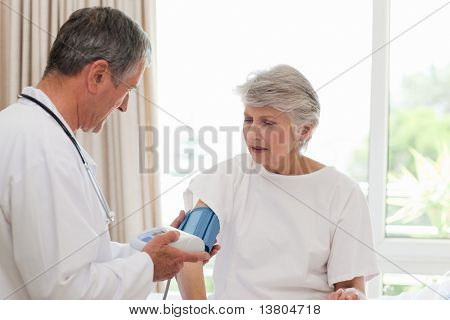 Doctor taking the blood pressure of his patient