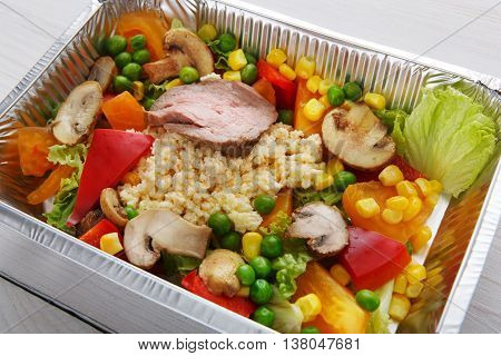 Healthy food and diet concept. Take away of fitness meal. Weight loss nutrition in foil boxes. Couscous with mushrooms, turkey meat and vegetables at white wood