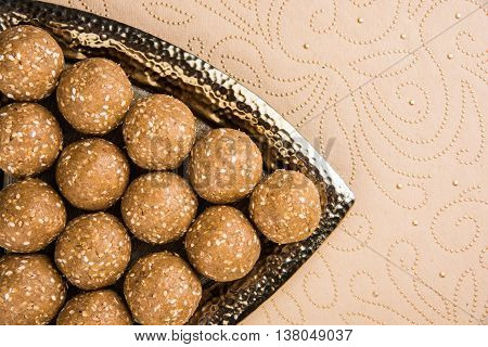 sesame laddu or tulgul or til gul laddu or ladu, favourite sweet dish in Makar Sankranti Festival in India, 14 january, indian festival sweets, served in triangle plate