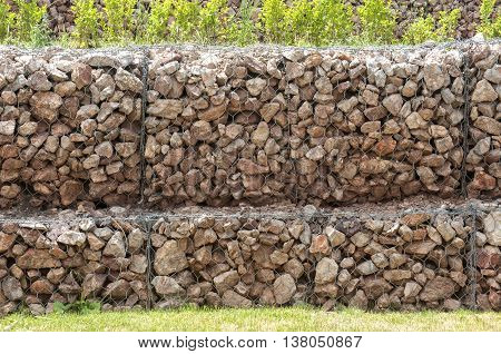 Hexagonal wire netting gabion box wall filled with stones closeup as background