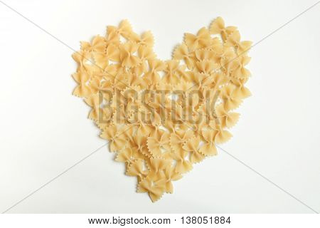 Heart made of farfalle bow-tie pasta on the white background with copy space