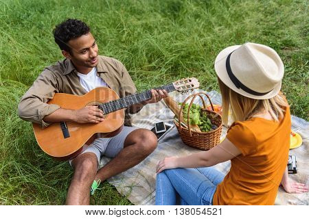 Enamored young man is playing guitar for his girlfriend. He is sitting and smiling. Couple is making picnic on grass