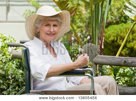 Mature woman in her wheelchair in the garden