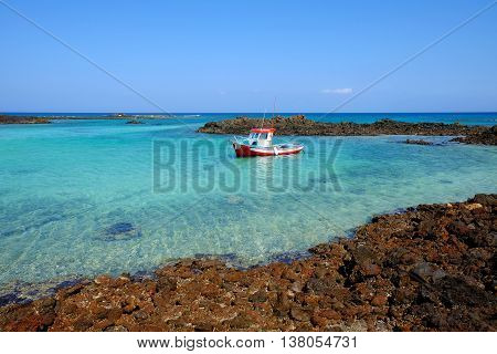 A white boat in a lagoon the crystal emerald water between the volcanic rocks on the island Lobos in Spain.