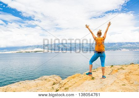 Woman hiker hiking with backpack arms outstretched looking at sea and mountains view. Accomplished climber with hands up outdoors. Beautiful inspirational landscape. Trekking and activity concept.