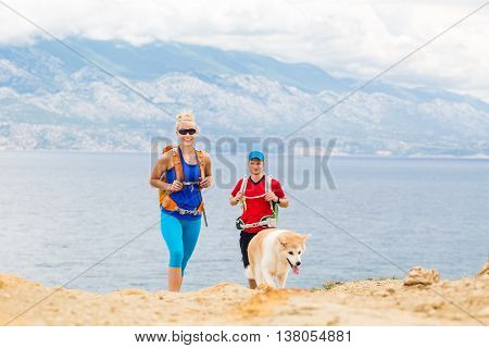Happy couple hikers trekking with akita dog in summer mountains at seaside. Young woman and man walking on rocky mountain trail path looking at beautiful inspirational landscape sea view.