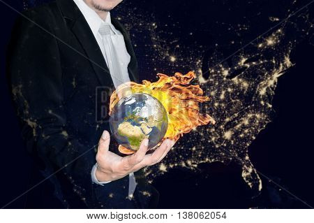Business man holding the burning global earth in his hands against america city night light.Global warming and ecology concept. (Elements of this image furnished by NASA)