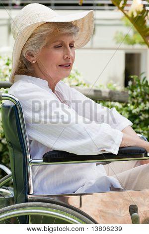 Mature woman in her wheelchair in the garden