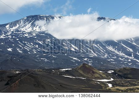 Volcanic landscape of Kamchatka Peninsula: beautiful summer view of cone of active Plosky Tolbachik Volcano and clouds partially hiding the top of volcano. Eurasia Russian Far East Kamchatsky Region Klyuchevskaya Group of Volcanoes.