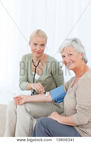 Lovely doctor taking the blood pressure of her patient