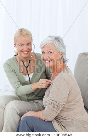 Enfermera tomando el heartbeat de su paciente en el hogar