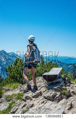 Single female hiker near bench at mountain summit with beautiful clear blue sky and copy space above her