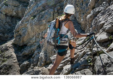 Female hiker with backpack, white helmet and safety rope, ascending while turning to look toward rocks