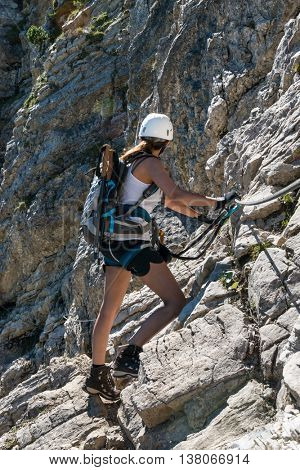 Single young woman in white helmet, backpack and climbing gear, carefully climbing side of mountain while looking away at daytime