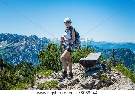 Confident single female hiker standing on stones beside bench at mountain peak under clear blue sky with copy space