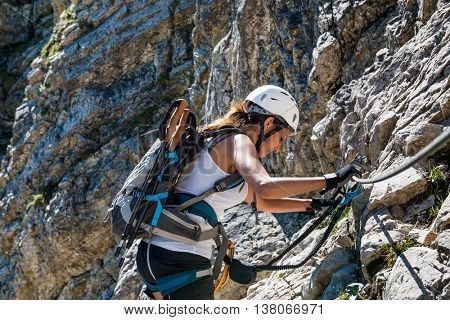 Fit athletic woman mountaineering climbing a steep rocky cliff face with the aid of ropes on a sunny summer day