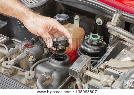 checking oil levels in service shop in a car
