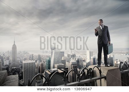 African businessman on a skyscraper using a mobile phone