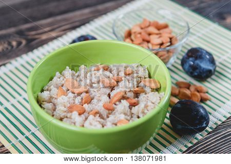 Porridge Oats with Nuts and Prunes on Wooden Table. Healthy Food Concept