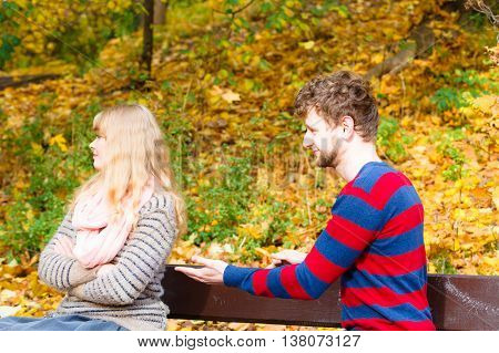 Two People Sit On Bench In Park Arguing.