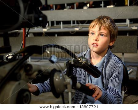 Little boy sits on the professional video camera in auditorium on television broadcast