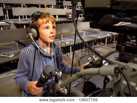 Niño con auriculares y micrófono se encuentra en la cámara de vídeo profesional en Auditorio Tel