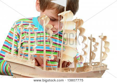 Small boy in striped shirt work with zeal on hull of artificial ship, focus on boat