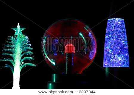 Three souvenir lamps of different form: conifer,  round  red and cylindrical blue  on black background.