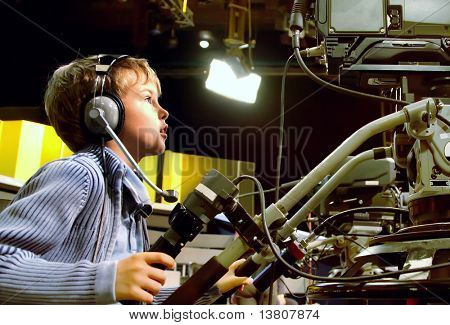 Little boy with headphones and microphone looks to professional video camera in auditorium on television broadcast
