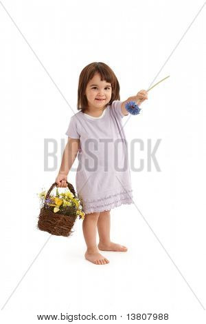 Cute girl in sweet dress handing blue flower, holding basket full of spring flowers, smiling.?