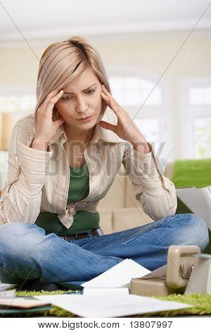 Unruhigen Betrieb Kopf der Frau sitzen am Boden des Wohnzimmers Dokumente betrachten.?