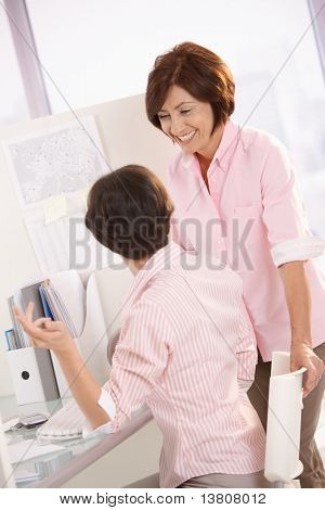 Happy female coworkers chatting at office desk, senior woman smiling.?