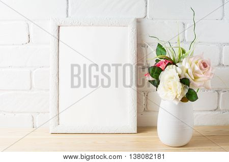 White frame mockup with tender pink roses bunch. Empty white frame mockup for design presentation. Portrait or poster frame mockup.