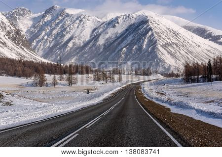 Scenic winter view from the asphalt road in the mountains covered with snow and trees on the side of the road on a background of blue sky and clouds