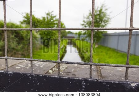 A metal outdoor fence overlooking a canal surrounded by grass bushes and trees.