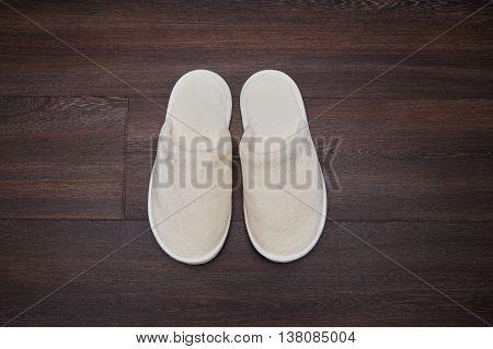 pair soft white slippers on wooden floor