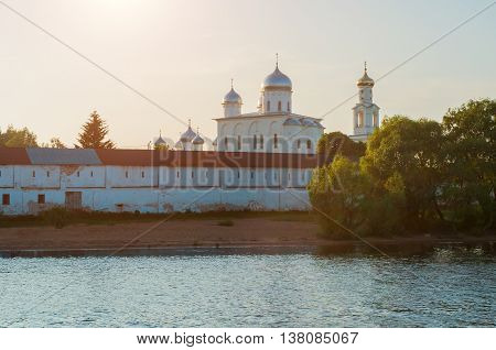 Sunset architecture landscape - view of cathedrals and bell tower in Yuriev male monastery on the bank of the Volkhov river in Veliky Novgorod Russia sunset summer architecture view in the backlight