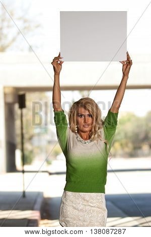Transgender female in green sweater holding up a blank poster board sign for advocation messages.