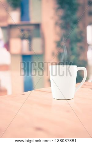 Vintage Filter : White Coffee Cup On Wood Table At Blur Cafe Background With Bokeh Light.