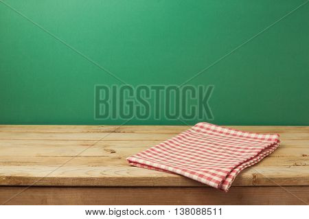Empty wooden vintage table with red checked tablecloth over green wall background