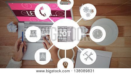 Smartphone apps icons against cropped image of woman with pen using laptop